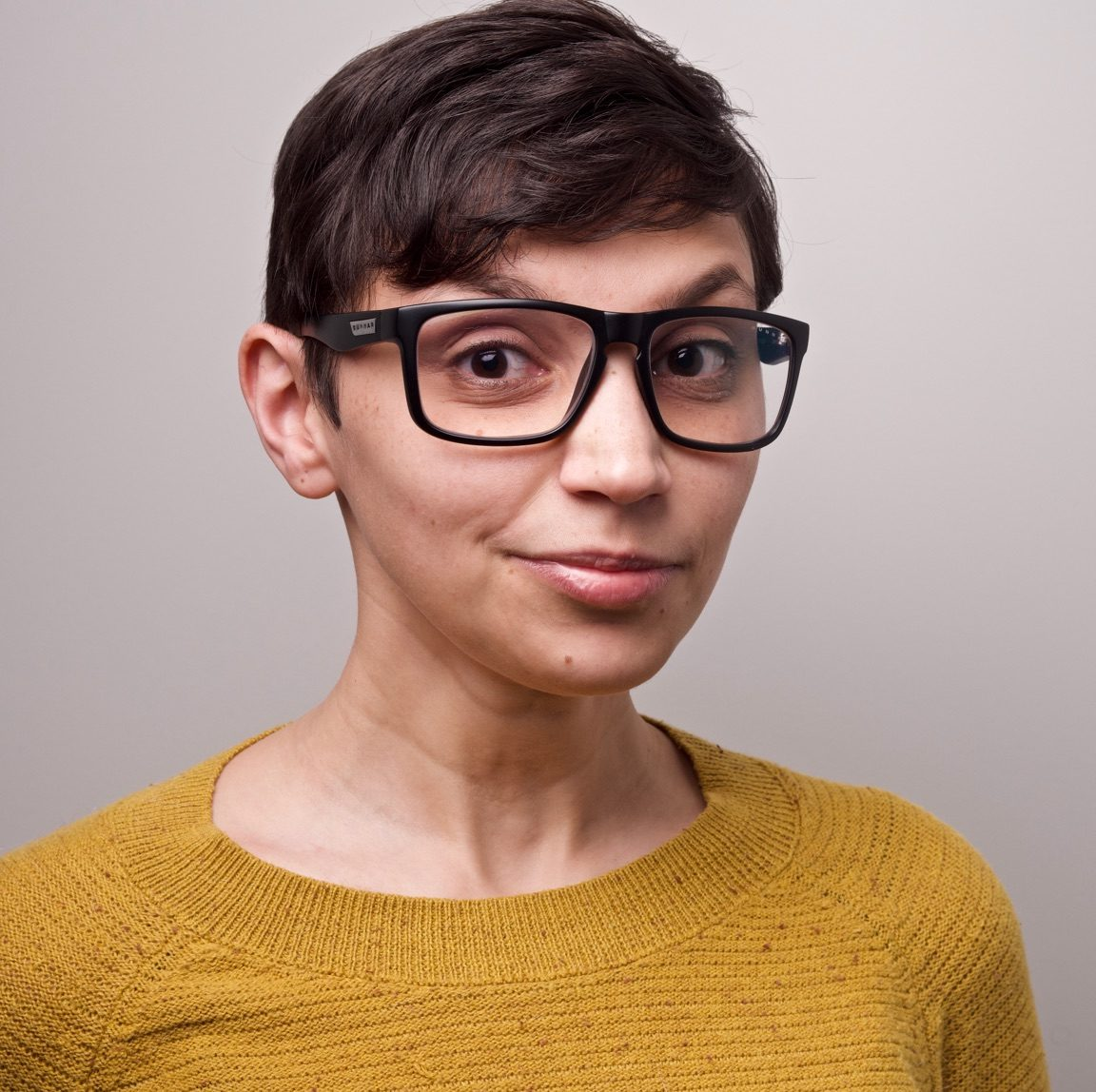 Woman with short brown hair wearing black-rimmed glasses.